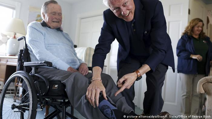 Bill Clinton shows George H. W. Bush wearing socks with Clinton's face on them