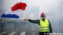 A protester wearing a yellow vest, a symbol of a French drivers' protest against higher diesel taxes, holds a French flag during clashes at the Place de l'Etoile near the Arc de Triomphe in Paris, France, December 1, 2018. REUTERS/Stephane Mahe