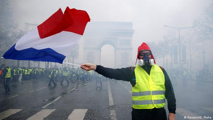 A protester flying the French national flag near the Place de l'Etoile
