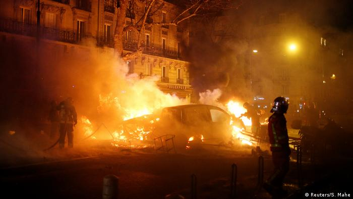 Firefighters extinguish burning cars set afire by protesters in Paris, France (Reuters/S. Mahe)