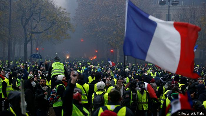 A French flag is held by protesters wearing yellow vests in Paris, France (Reuters/S. Mahe)