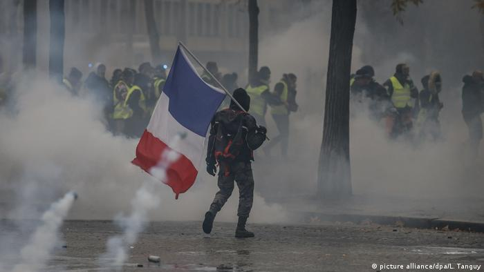 A demonstrator holds a French flag during clashes with riot police (picture alliance/dpa/L. Tanguy)