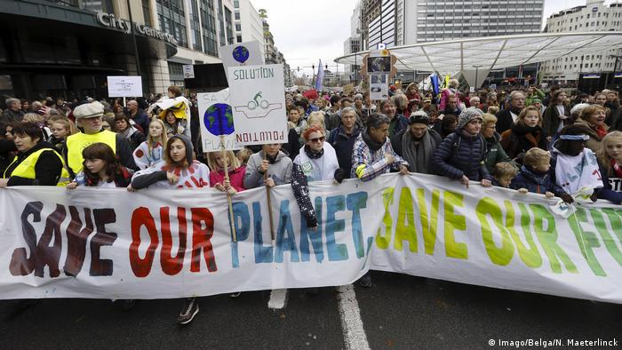Protesters in Brussels hold a sign saying 'Save our planet'