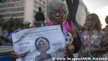 Senhora segura um jornal local que estampa o rosto de Marielle Franco na capa durante protesto