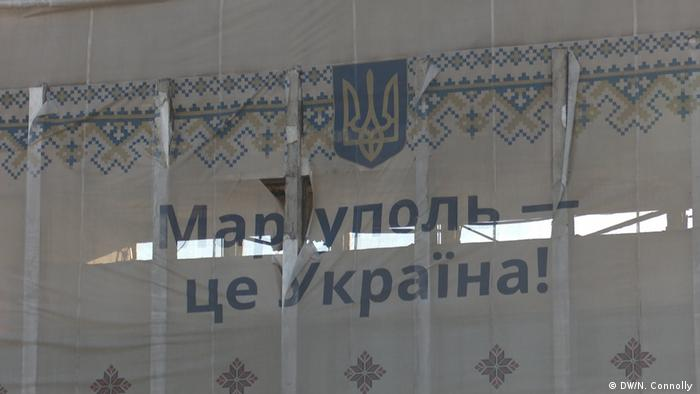 A banner that reads Mariupol is Ukraine!' hangs on the ruins of the city hall building