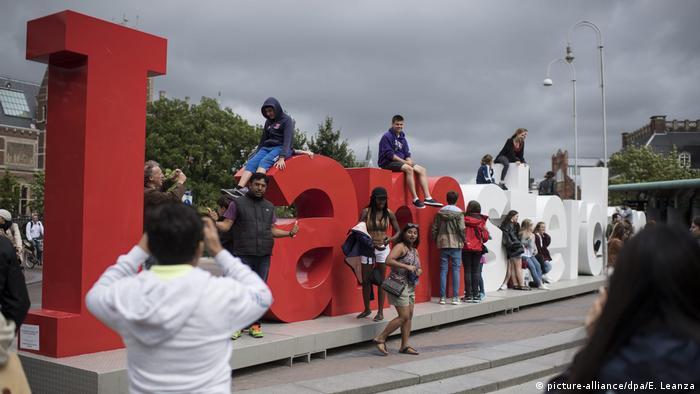 Pessoas posando para fotos no letreiro I Amsterdam