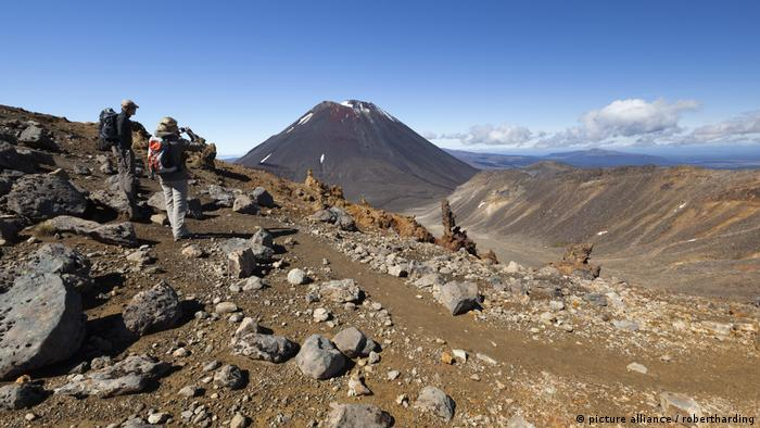 New Zealand, Tongariro Alpine Crossing. Hikers admire the view of a mountain.