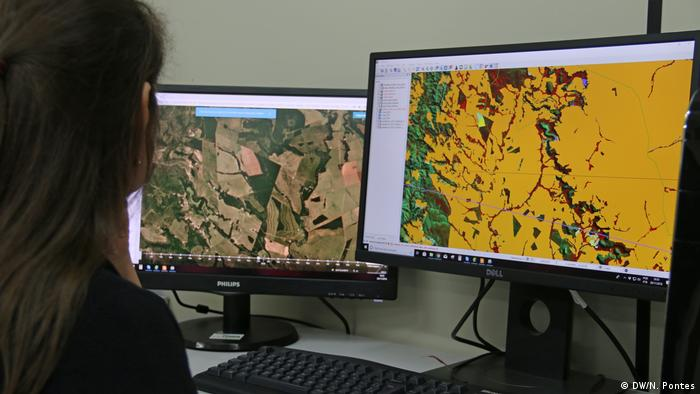 A woman looks at two computer screens showing satellite images of deforestation in the Amazon