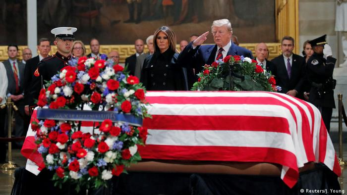 U.S. President Donald Trump salutes as he and First Lady Melania Trump pay their respects