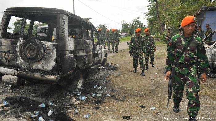 Indonesian soldiers walk by a burned out vehicle following clashes in Papua province