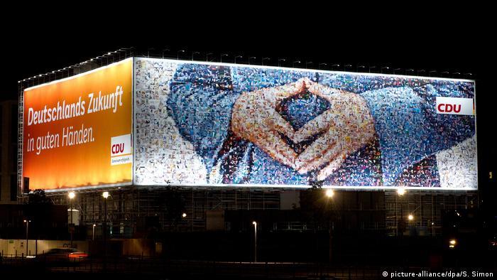 Cartaz com propaganda eleitoral da CDU mostra famoso sinal de losango feito por Merkel.