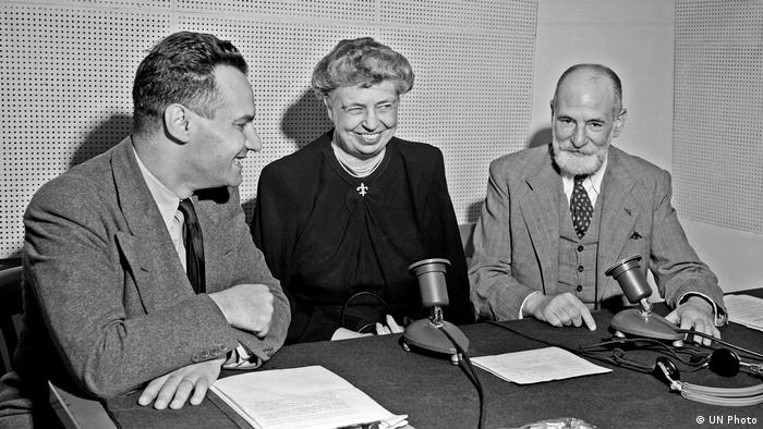 Three people sitting around a table with microphones