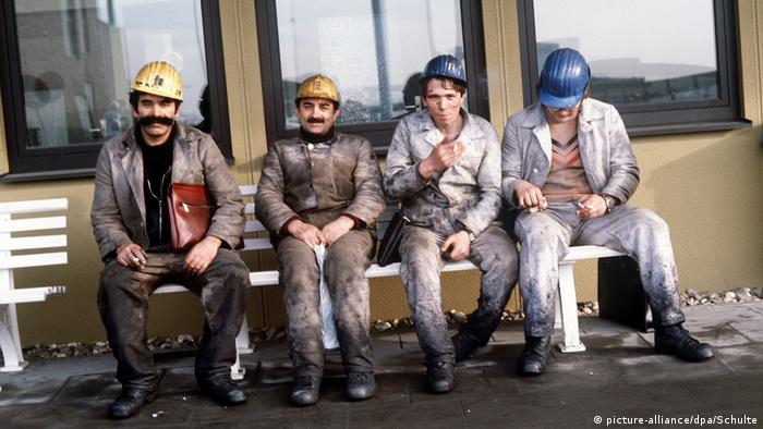 Turkish guest workers resting after work on a bench