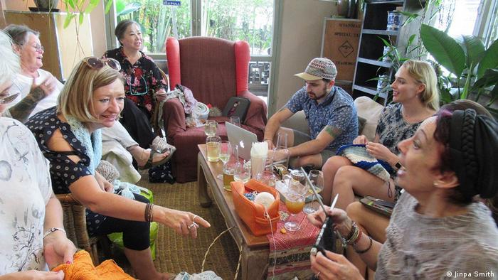Eine Gruppe von Menschen, die um einen Tisch sitzen und stricken