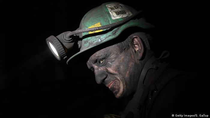 Face of a miner in the darkness, deep down in a coal mine