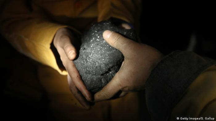 Hands holding a piece of coal