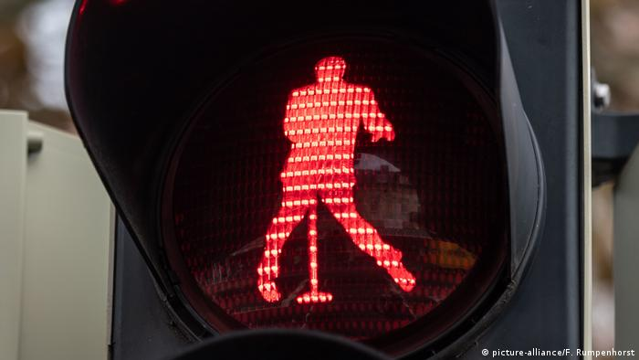 A red traffic light showing Elvis Presley standing at a microphone