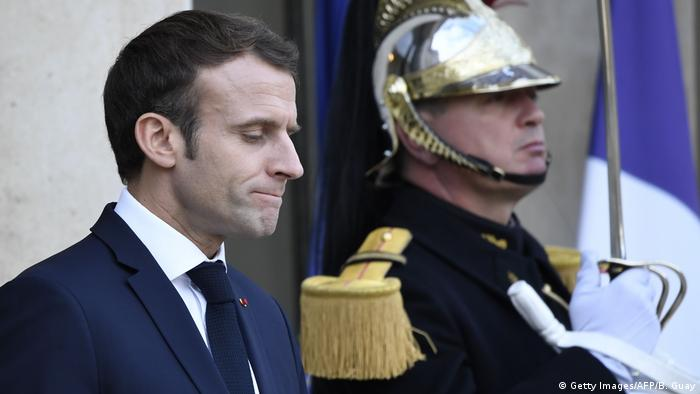 Macron presses his lips together and looks down as he stands next to a guard (Getty Images/AFP/B. Guay)