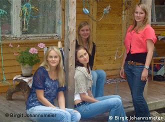 Junge Livinnen sitzen auf der Veranda vor einem Haus (Foto: Birgit Johannsmeier)