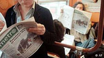 Commuters reading newspapers on a bus