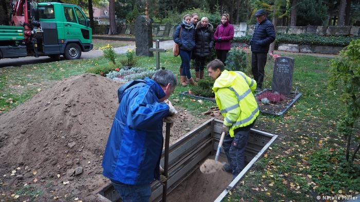 A green cemetery, where the Ranisch family looks on as undertakers dig up Christoph's grave