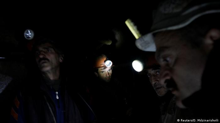 Tkibuli miners working with safety lamps