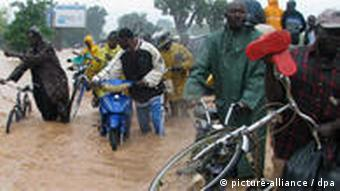 Residents in west Africa carry their bicycles after floods