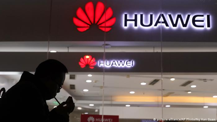 A man lights a cigarette outside a Huawei retail shop in Beijing