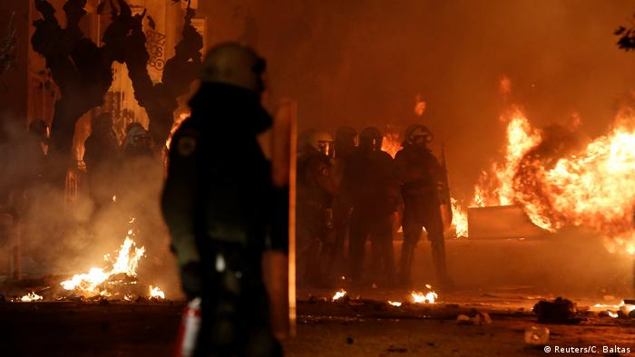 Riot police standing between fires in Athens