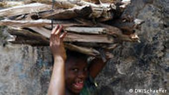 A young girl in Freetown, Sierra Leone carries firewood on her head
