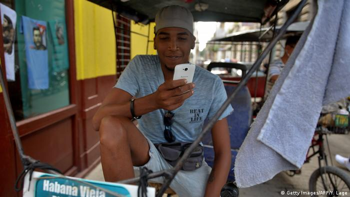 A Cuban man looking at his smartphone (Getty Images/AFP/Y. Lage)