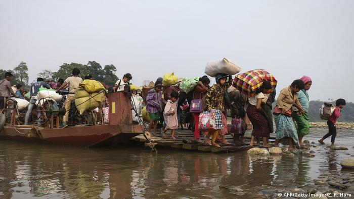 People flee across the Malikha river in Myanmar on a wooden ferry carrying belongings over their shoulders