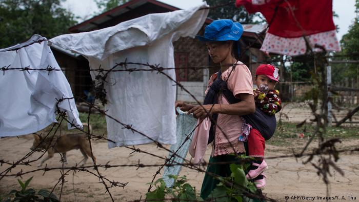 A woman with a child on her back hangs laundry out in a temporary internal displacement camp in Kachin state, northern Myanmar