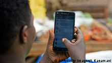 A woman is seen going through her phone in Kampala