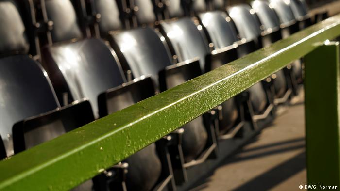 Green handrail along the side of a row of stadium seats