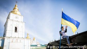 Девушка с флагом Украины на фоне церкви в Киеве