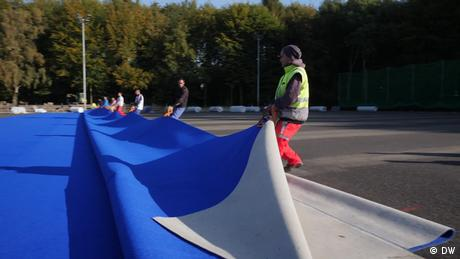 A blue plastic sports surface is rolled out. (DW)