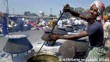 NAGPUR, INDIA: An Indian volunteer cook squints from the effects of smoke and heat as he stirs a big pot of food to be distributed to several hundreds of people in the streets of Nagpur, 23 October 2004, as part of the Dassera-Durga (9 nights) festival, when people who have been fasting break their fast. The annual festival of Dassera-Durga is celebrated with the slaying (the burning of an effigy) of the ten-headed king of Lanka Ravana at the hands of Rama the hero of the good and evil epic Ramayana. AFP PHOTO/Rob ELLIOTT (Photo credit should read ROB ELLIOTT/AFP/Getty Images)