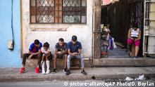 People surf the internet on their smartphones on the sidewalk in Havana, Cuba, Thursday, Dec. 6, 2018. For the first time, Cubans are able to sign up for 3G internet service for their mobile phones, with packages ranging from 600 megabytes for about $7 to four gigabytes for about $30 month. (AP Photo/Desmond Boylan) |