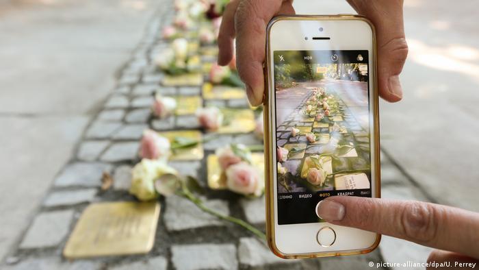 Com o celular, pessoa tira foto de uma série de Stolpersteine instaladas em calçada