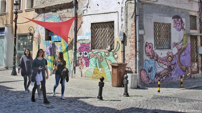 Young people pass street art