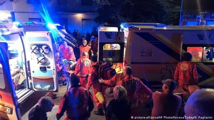 Italian emergency service workers load victims into ambulances