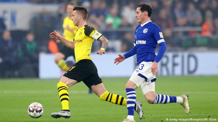 BVB's Marco Reus dribbles the ball away from Schalke's Sebastian Rudy, 08.12.2018. (Getty Images/Bongarts/M. Rose)