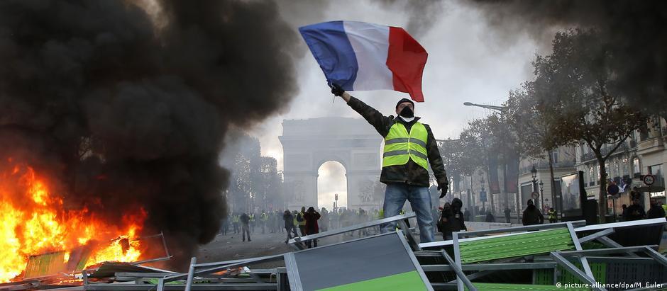 """Manifestante dos """"coletes amarelos"""" ergue a bandeira da França em barricada na avenida Champs-Élysées, em Paris"""