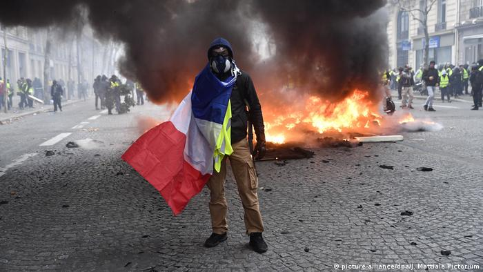 A man in a gas mask with a french flag stands in front of burning debris in Paris (picture-alliance/dpa/J. Mattiale Pictorium)