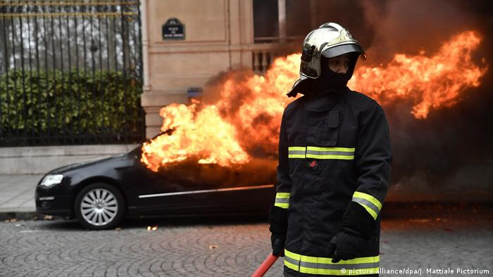 Fireman standing in front of a burning car