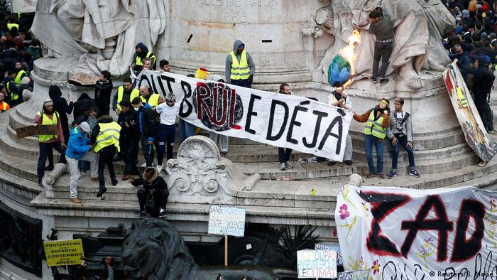 'Everything is already burning,' says a banner held by protesters at the Place de la Republique