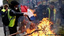 A protester wearing a yellow vest burns a French flag at a barricade during clashes with police as part of a national day of protest by the yellow vests movement in Paris, France, December 8, 2018. REUTERS/Stephane Mahe