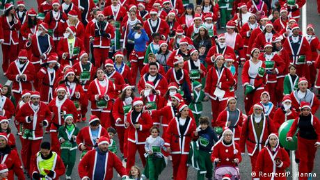 Santa Clauses and green elves on the streets of Madrid