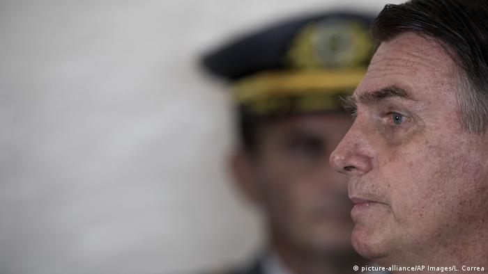 Foto de perfil de Jair Bolsonaro frente a un militar